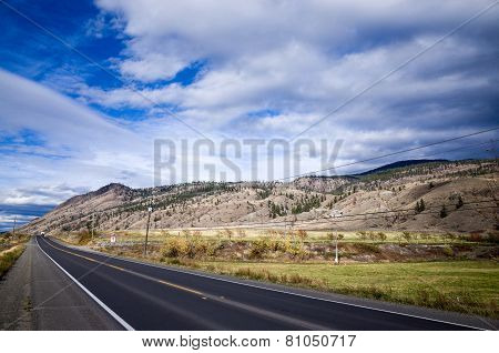 Empty Asphalt Highway Through Mountainous Country