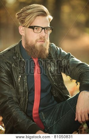 Close up picture of a fashion man relaxing in the park, looking away from the camera.