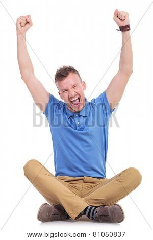 casual young man sitting on the floor with his legs crossed and cheering with both hands raised in the air. isolated on white