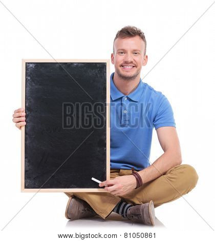 picture of a casual young man sitting on the floor with his feet crossed while holding a small blackboard and pointing at it with a piece of chalk. on a white background