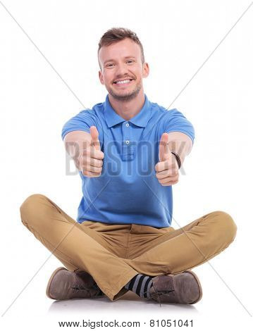 casual young man sitting on the floor with his legs crossed and showing thumbs up gesture with both hands while smiling for the camera. isolated on white