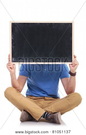 picture of a casual young man sitting on the floor with his feet crossed while holding a small blackboard in front of his face. on a white backgroun