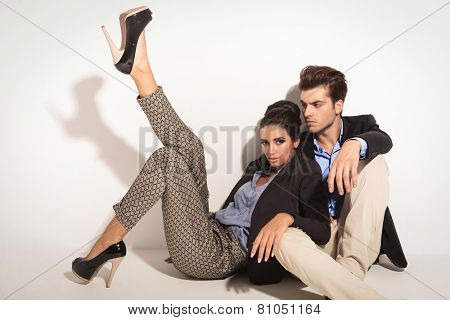 Sexy fashion woman leaning on her lover and holding one leg up while he is looking away from ther camera. Both are sitting on ther floor.
