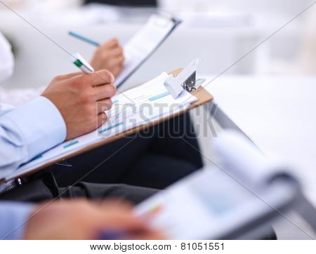 Business people sitting and writting at business meeting