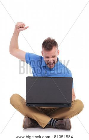 casual young man sitting on the floor with his legs crossed and cheering while looking at his laptop. isolated on white