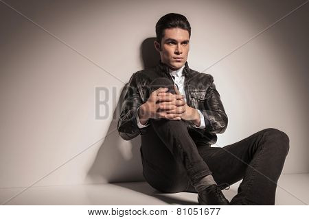 Picture of a young casual man resting on the floor while holding his knee up with both hands. Looking away from the camera.