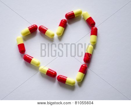 Red And Yellow Capsule In The Form Of Heart On A Light Background