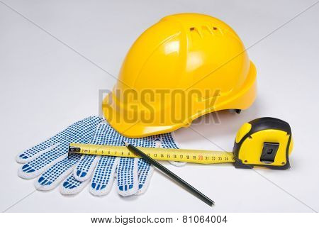 Builder's Tools - Helmet, Work Gloves, Pen And Measure Tape  Over White