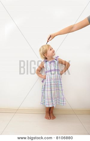 Mother Measuring Height Of A Child