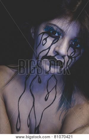 representation of sadness, beautiful woman with painted tears on the face