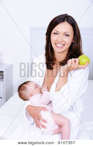 Woman With Green Apple Breastfeeding Her Baby