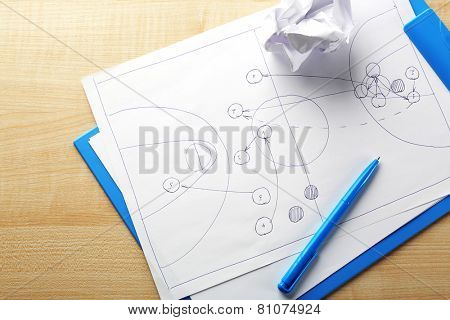 Scheme football game on clip board paper with crumpled ball and pen on wooden table background