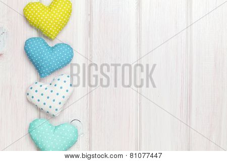 Valentines day toy hearts over white wooden background with copy space