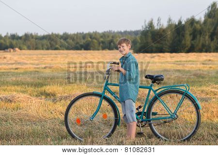 Smiling Teenager Boy Holding Bicycle In Farm Field