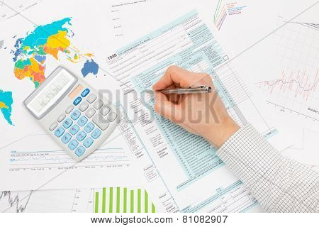 Male Filling Out 1040 Us Tax Form With Lots Of Financial Documents Around
