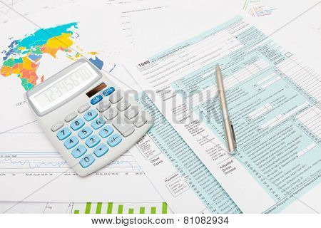 Calculator And Silver Ball Pen Over Us 1040 Tax Form