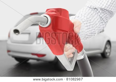 Red Color Fuel Pump Gun In Hand With Grey Car On Background