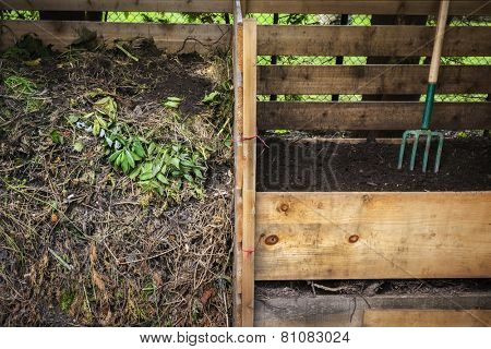 Large cedar wood compost boxes with composted soil and yard waste for backyard composting