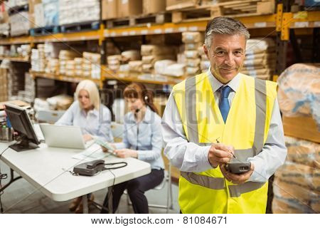 Smiling manager wearing yellow vest using handheld in a large warehouse
