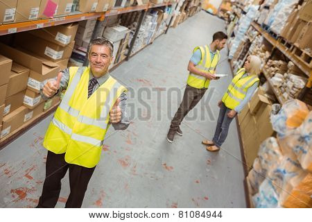 Warehouse manager smiling at camera showing thumbs up in a large warehouse
