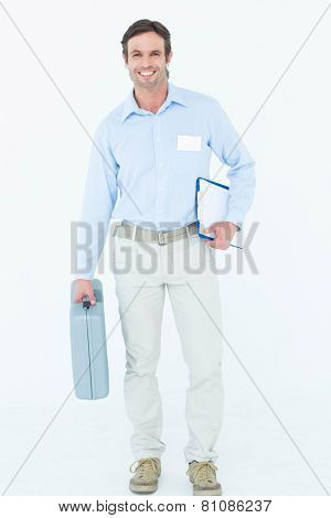 Portrait of confident supervisor carrying tool box and clipboard over white background
