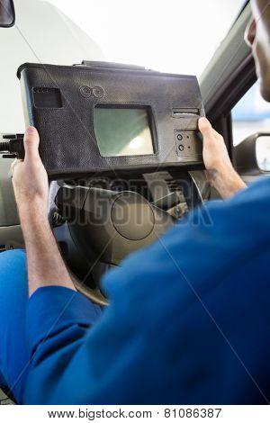 Mechanic using diagnostic tool in the car at the repair garage