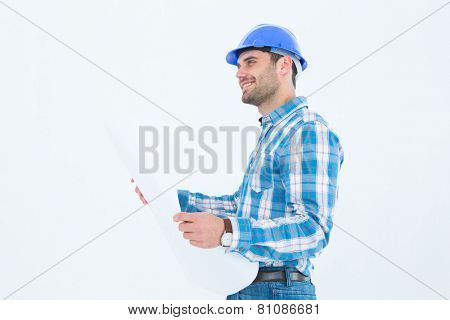 Smiling engineer looking away while holding blueprint against white background
