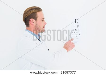 Optician in coat pointing eye test on white background