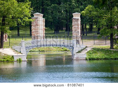 The small shabby bridge in park over a pond. Gatchina. Petersburg. Russia.