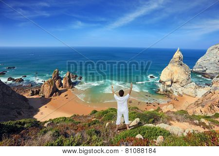 Small beautiful beach on the Atlantic coast. Middle-aged woman dressed in white doing yoga. The seaside resort of Sintra