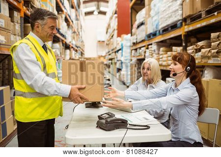 Manager wearing yellow vest giving box to his colleague in a large warehouse
