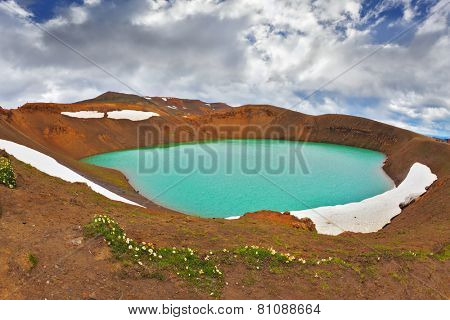 Picturesque Summer in Iceland. Lake in the crater of an extinct volcano. Lake water bright green color. On the shores lie snowfields from last year