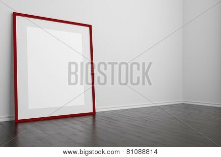 Red empty frame standing on floor in an empty room (3D Rendering)
