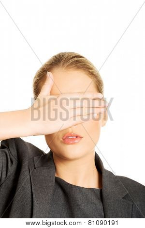 Blonde woman covering her face with both hands