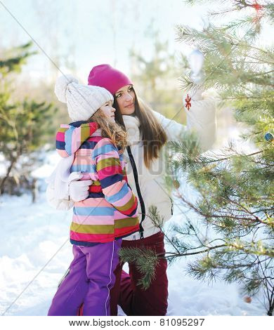 Winter And People Concept - Mother With Child Decorate A Christmas Tree Outdoors