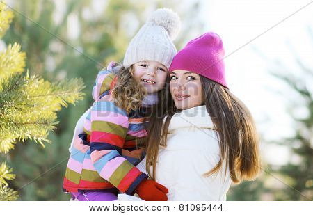 Winter And People Concept - Portrait Of A Happy Mother And Child Outdoors In Winter Day