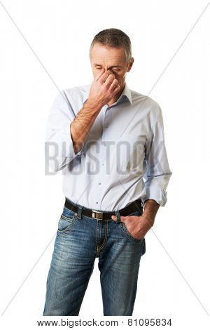 Mature man holding his nose because of sinus pain.
