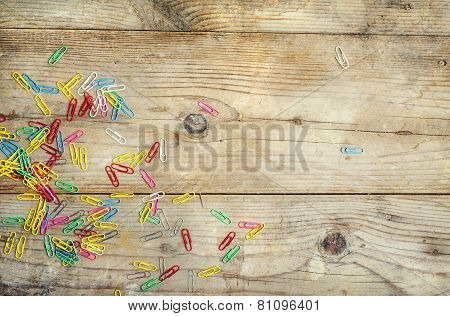 Colorful paperclips on wooden floor