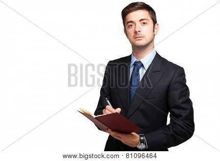 Young male manager writing on his agenda