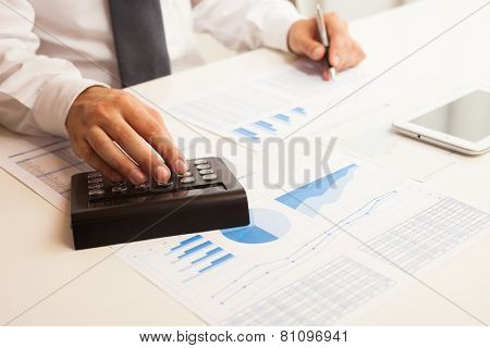 Accountant checking numbers on a business document while using a calculator