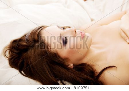 Beautiful woman lying down on the bed.