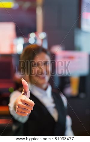 Barmaid showing thumbs up to camera in a bar