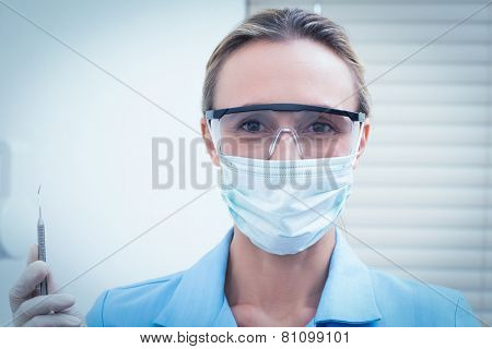 Portrait of female dentist in surgical mask and safety glasses holding injection