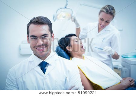 Portrait of smiling male dentist with assistant examining womans teeth in the dentists chair