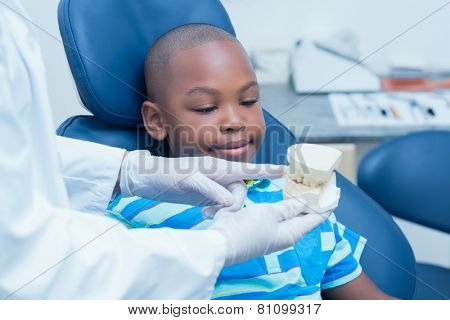Cropped dentist showing young boy prosthesis teeth in the dentists chair