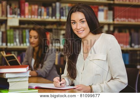Smiling pretty brunette student writing in notepad in library