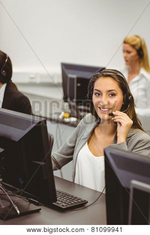 Smiling call centre agent talking on the headset in the office