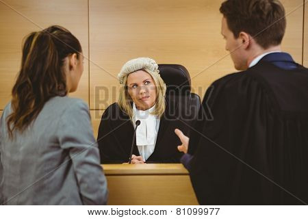 Judge wearing dress and wig listening lawyers in the court room