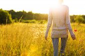 picture of sun flare  - Young woman walking in the field toward the sun holding a poppy flower - JPG