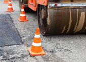 image of paved road  - Tandem road roller and traffic cones on the road construction - JPG